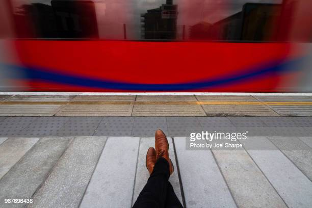 pov of a man waiting for a train in london - red tube stock pictures, royalty-free photos & images
