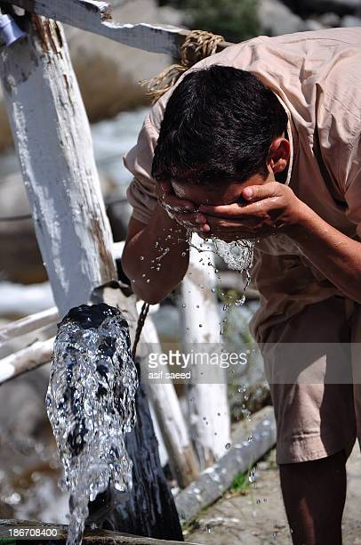 CONTENT] a man washing his face with clear and cold spring water in northern Pakistan