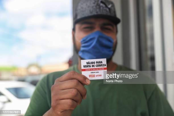 a man who has been waiting in line for hours shows a ticket to buy beer on May 1 2020 in Hermosillo Mexico A few stores in Hermosillo and the...