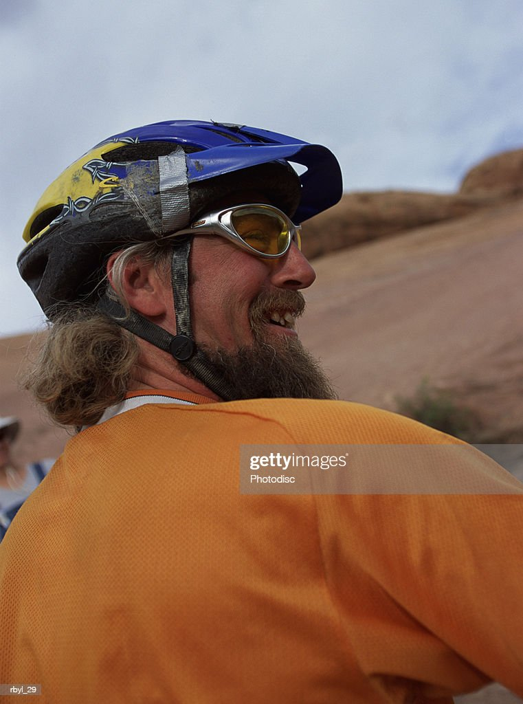 a man with a long beard and bicycle helmet is smiling happily with the southern utah desert and sky in the background : Foto de stock