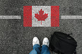 a man with a shoes is standing next to flag of Canada