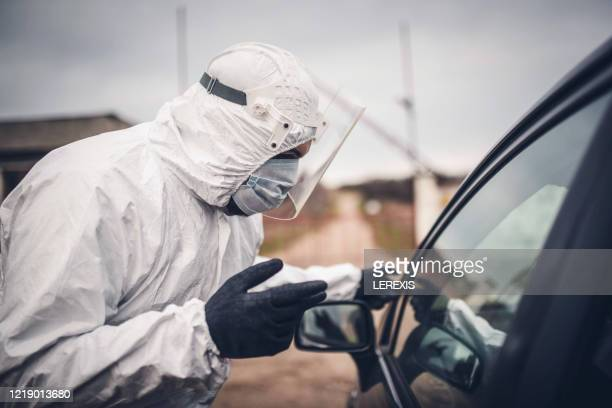 a man with protective clothing checks for sick at the border - lerexis stock pictures, royalty-free photos & images