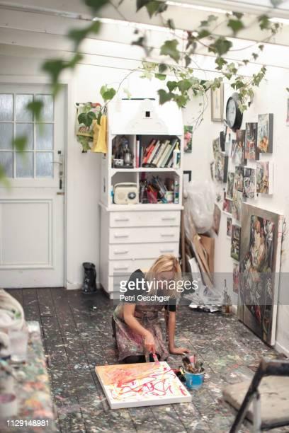 en mogen kvinna målning i hennes konststudio hemma. - canvas bildbanksfoton och bilder