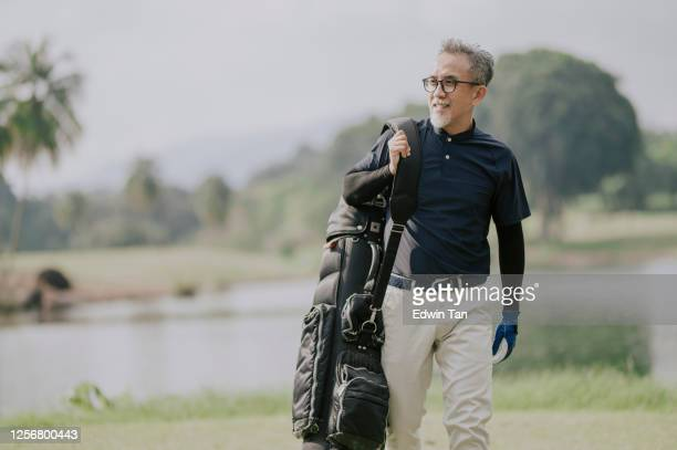 a matured chinese man golfer carrying a golf bag looking away in the golf course - golf stock pictures, royalty-free photos & images