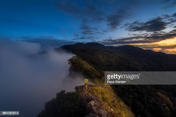 a Men standing on cliff lookout to scenic landscape