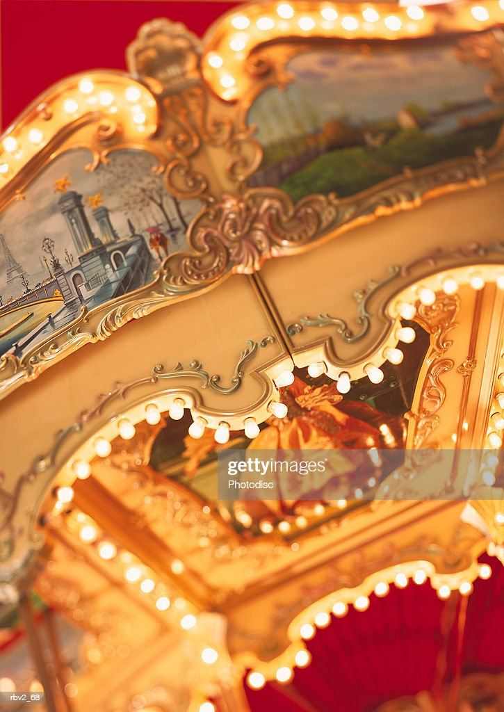 a merry-go-round ceiling is light up with paintings : Foto de stock