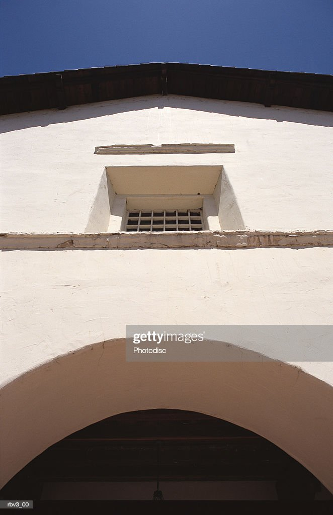 a mexican style white stucco wall with window and arch under a blue sky : Foto de stock
