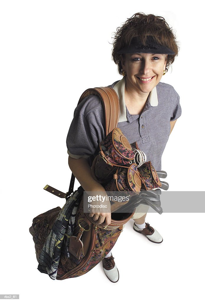 a middle age adult caucasian female golfer stands with her bag of golf clubs smiling and looking up at the camera : Foto de stock