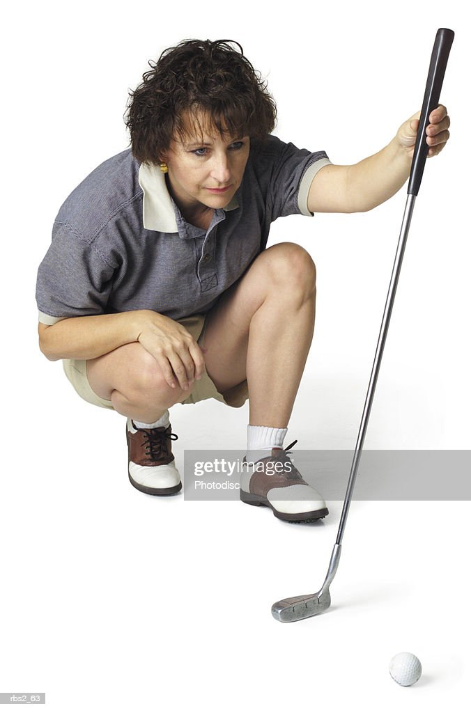a middle age caucasian female golfer in a stripped shirt crouches down with her putter and lines up a shot : Stockfoto