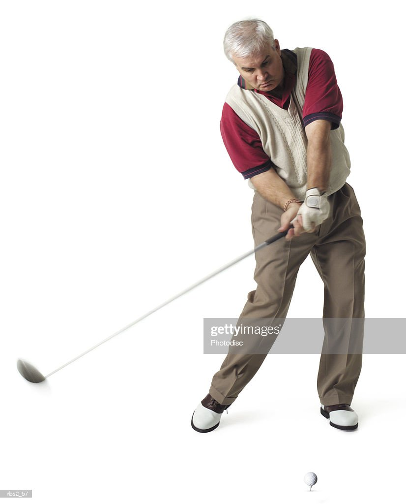 a middle age man with white hair is wearing a tan vest over a red golf shirt as he swings at a golf ball on a tee : Stockfoto