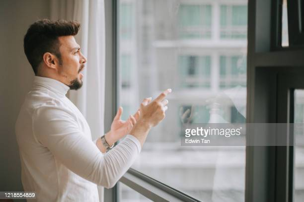 a middle eastern man talking to the window with digital screen displayed practicing presentation preparation - practicing stock pictures, royalty-free photos & images
