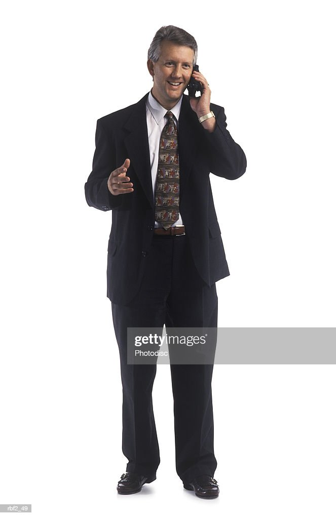 a middle-aged executive dressed in a black suit and tie talks over a cell phone as he motions with his hands : Stockfoto