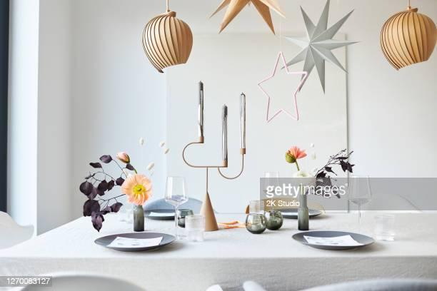eine moderne und einfach gestaltete weihnachtstischdekoration mit adventskranz, sternen und blumen in hoher auflösung fotografiert - dekoration stock-fotos und bilder
