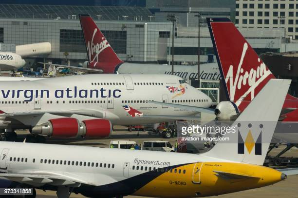 a Monarch Boeing 757200 three Virgin Atlantic 747400s parked at the terminal behind