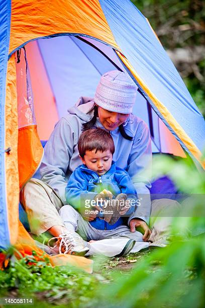 a mother and son sit in a blue and orange tent, and put their shoes on, at their campsite which is at approximately 10,120 feet along the Williams Creek trail (trail number 587).
