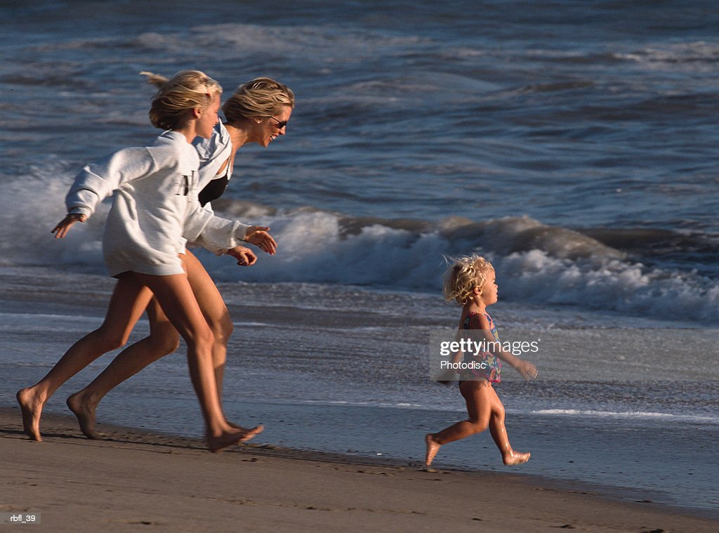a mother and teenage daughter run after a toddler on the beach : Stockfoto