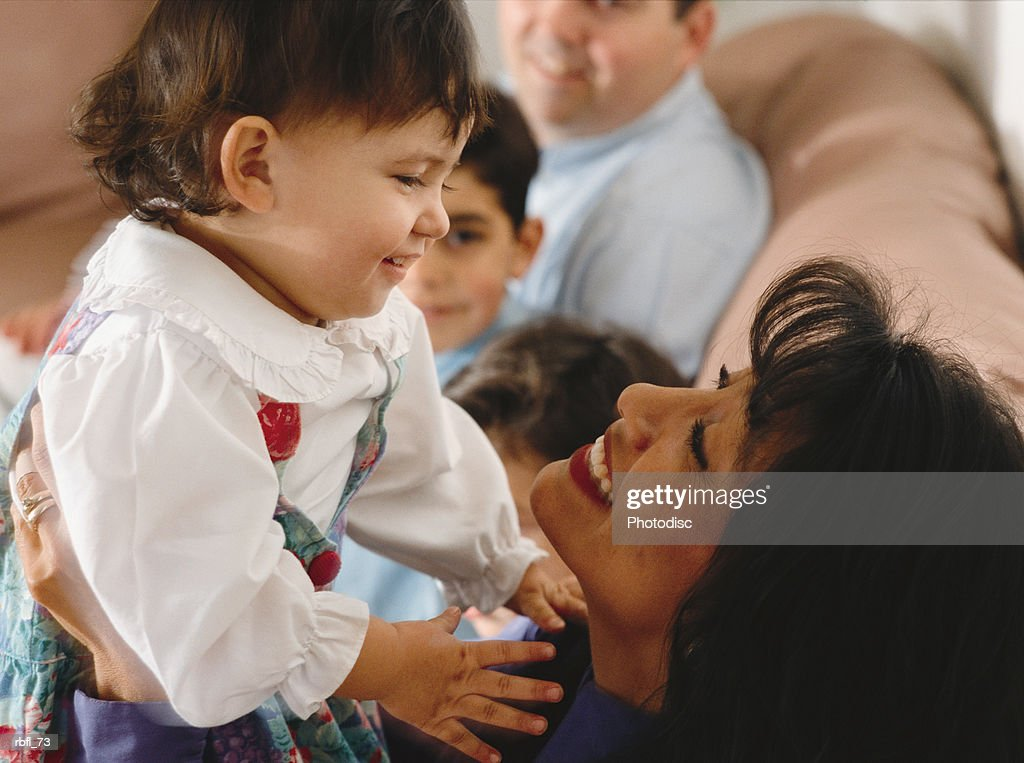 a mother holds her small daughter eye to eye at a family activity : Stockfoto