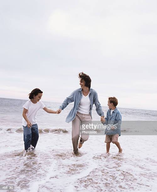 a mother holds her two son's hands on the seashore
