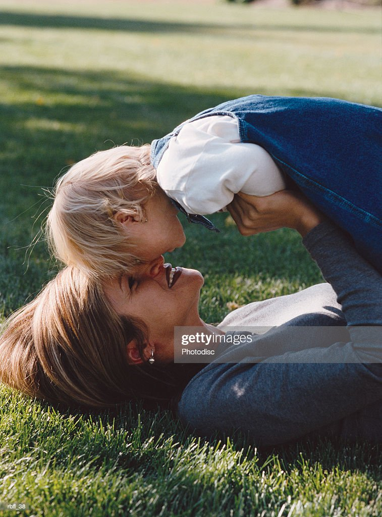 a mother lies down on the lawn as she rubs noses with her young child : Stockfoto