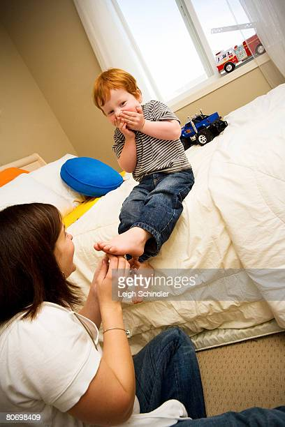 a mother tickles her son's feet. - tickling feet stock photos and pictures