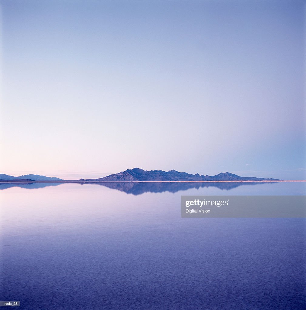 a mountain range reflects in a body of water with a pink and blue hue : Stockfoto