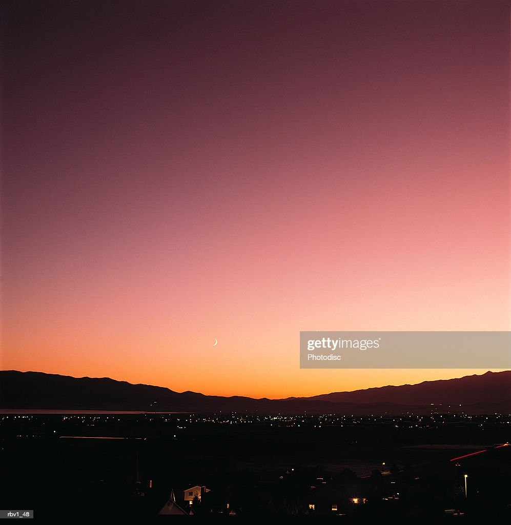 a multicolored sky is shown as the sun sets over a dark valley filled with homes : Foto de stock
