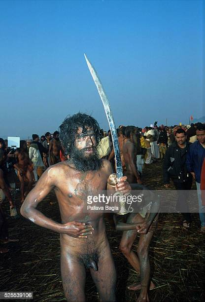 a naked sadhu rubbing sand after and brandishing a sword