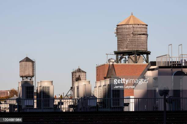 a new york city water tower on top of a building - water tower storage tank stock pictures, royalty-free photos & images