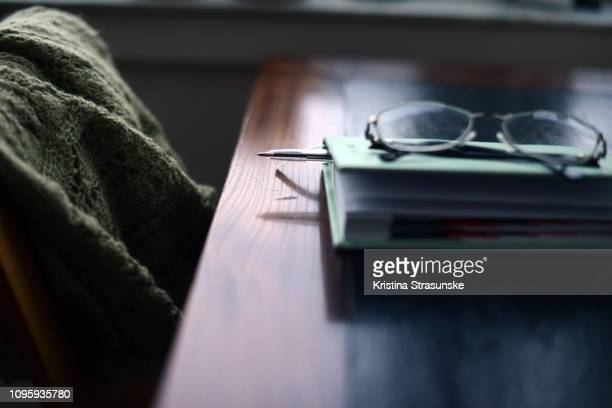a note pad and reading glasses on a desk, by a chair with a cardigan - kristina strasunske stock photos and pictures