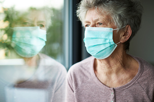 a old woman or grandma is wearing a respirator or surgical mask and looking out of the window 1213152647