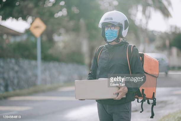 a package delivery senior man delivering the package carton to his client in the morning