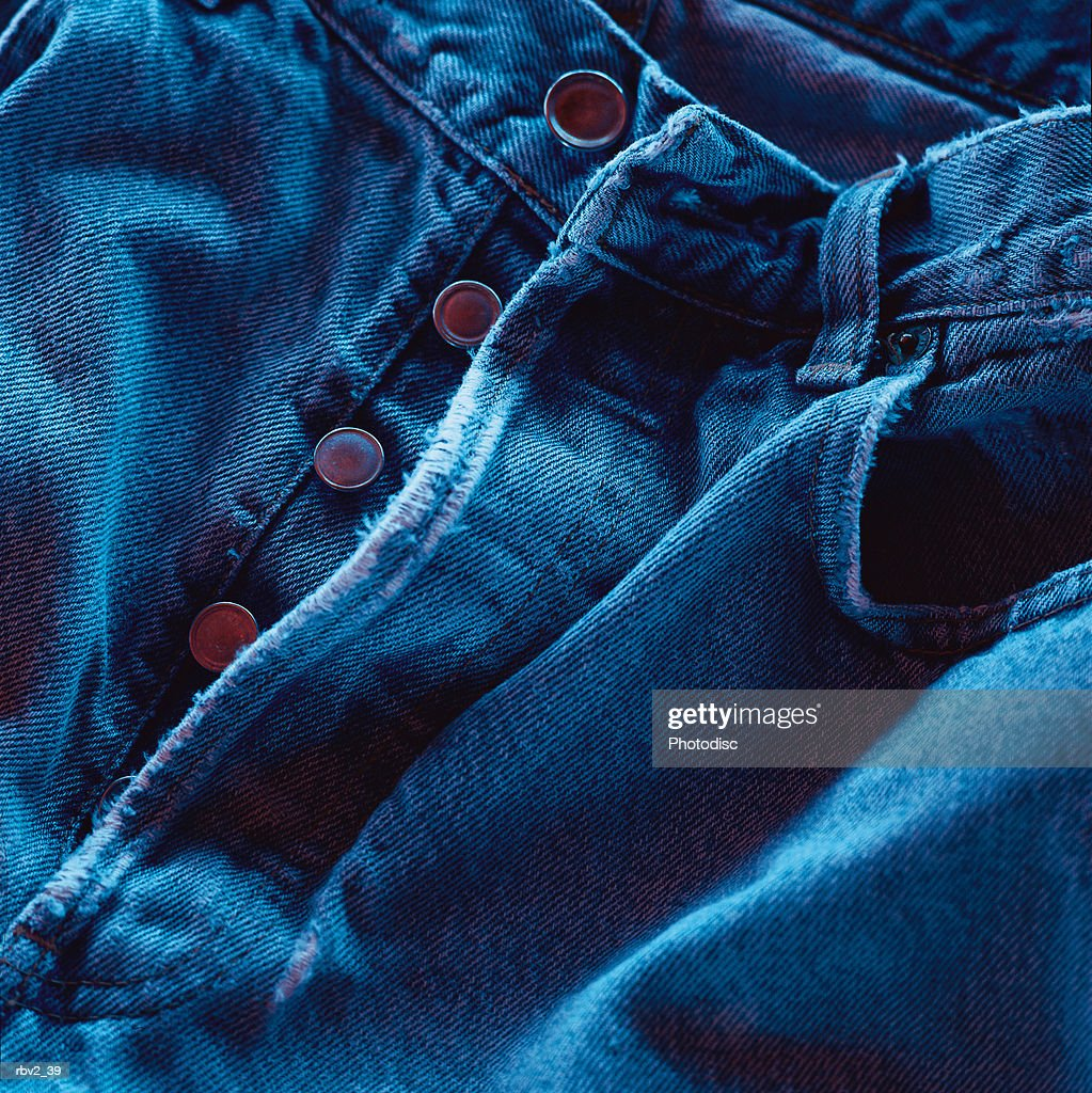 a pair of button fly denim jeans : Foto de stock