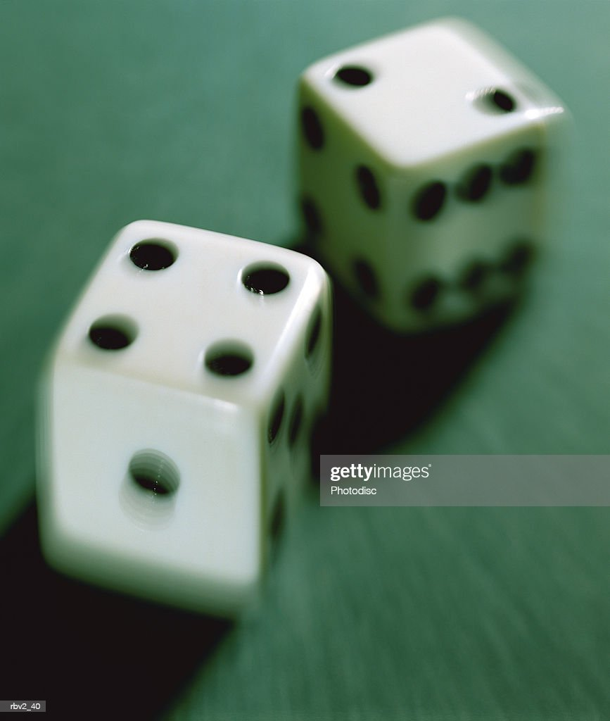 a pair of dice cast shadows on a green surface : Foto de stock