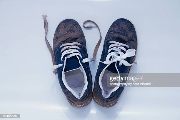a pair of muddy blue trainers / sneakers