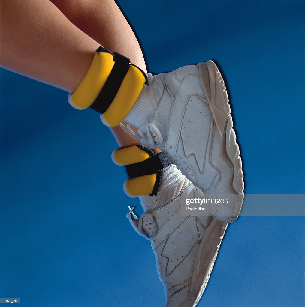 a pair of white shoes and yellow ankle weights rest on legs in front of a blue background : Foto de stock