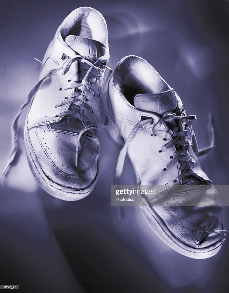 a pair of white tennis shoes with undone shoe laces sit next to each other as light casts shadows : Foto de stock