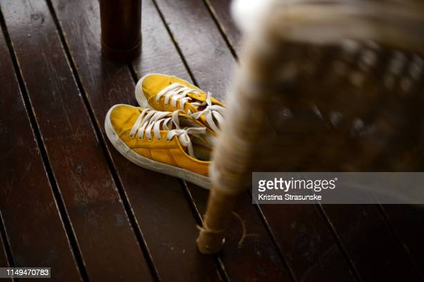 a pair of yellow canvas shoes on a dark wooden floor - 椅子 無人 ストックフォトと画像