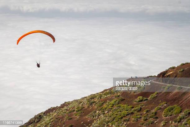 a paraglider on a red with yellow stripes paraglider flies in sky with white clouds, tenerife, teide - white stripes stock pictures, royalty-free photos & images