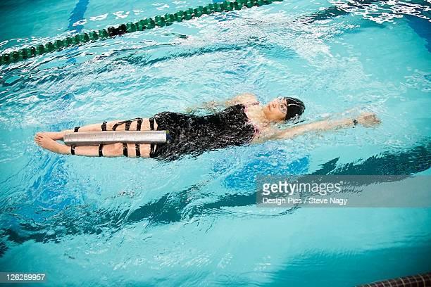 a paraplegic woman swims in a pool