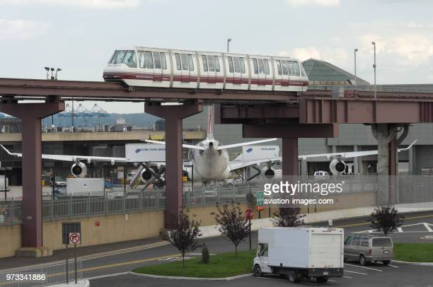 A passenger monorail with an Air France Airbus A340 parked at the terminal and Flying Food catering trucks behind.