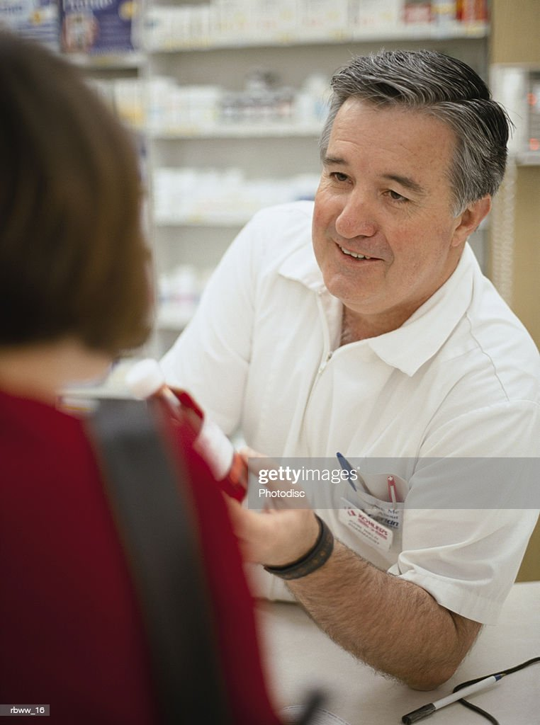 a pharmacist helps a customer with her prescription medication : Foto de stock