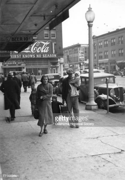 a photograph entitled 'Poverty Knows No Season' showing a young family consisting of a couple and three young children walking north on Broadway and...
