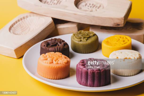 a plate full of mooncakes with exquisite flora pattern and different kind of wood mooncake molds against yellow background - moon cake stock pictures, royalty-free photos & images