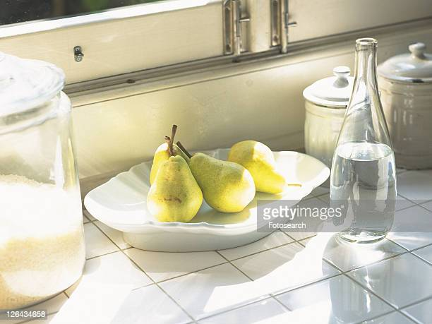 a Plate With Several Pears, Next to a Bottle and Some Pots, High Angle View