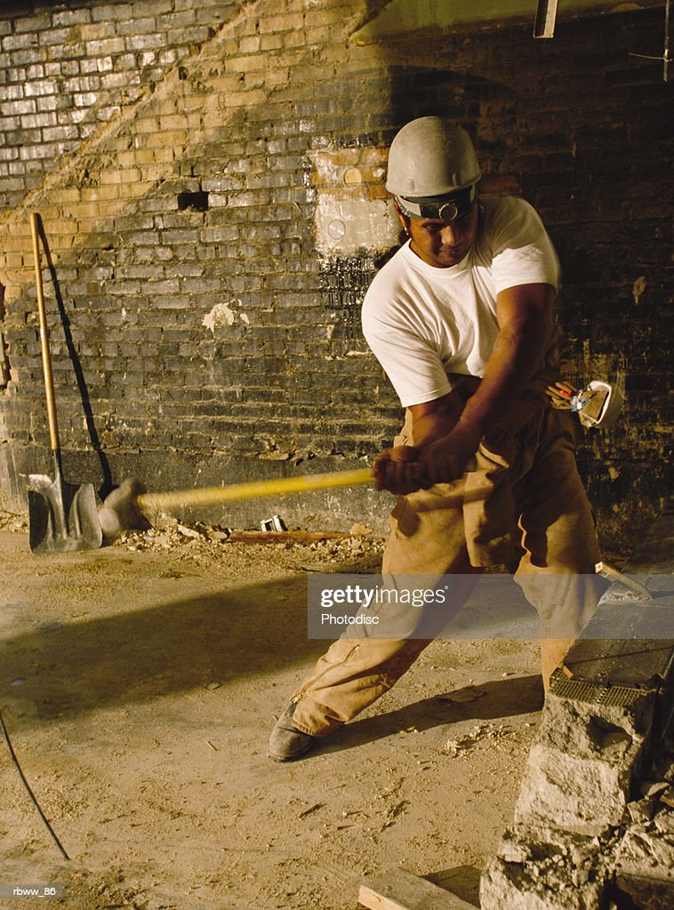 a polynesian male constuction worker swings a sledgehammer at a cement wall : Foto de stock