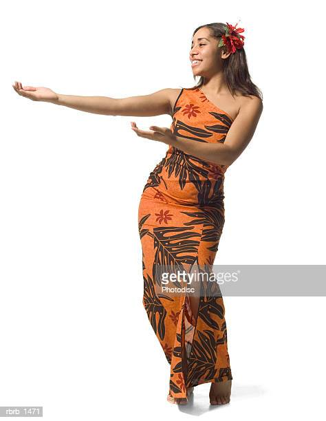 a polynesian teenage female in an orange floral dress does a traditional dance