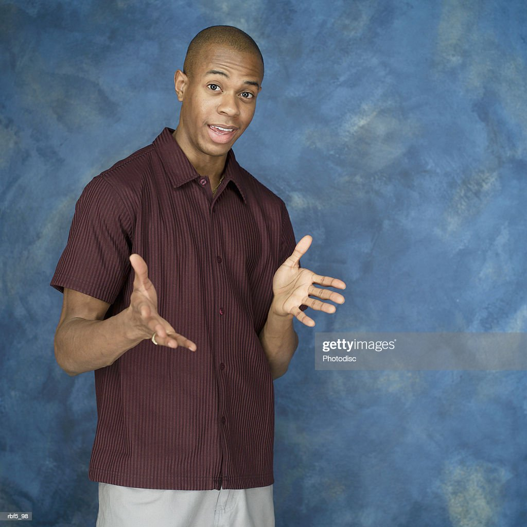 a portrait of a african american man in a purple shirt with his hands open and at chest level smiling at the camera : Stockfoto