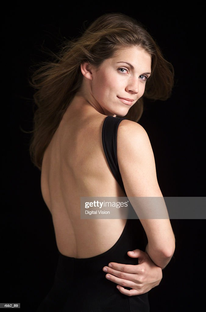 a portrait of a beautiful caucasian woman in black backless dress folding her arms turns around and looks at camera while her hair flows in the wind : Stockfoto