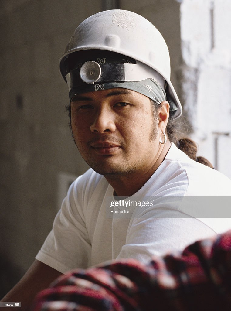 a portrait of a polynesian male construction worker in a white hard hat : Foto de stock