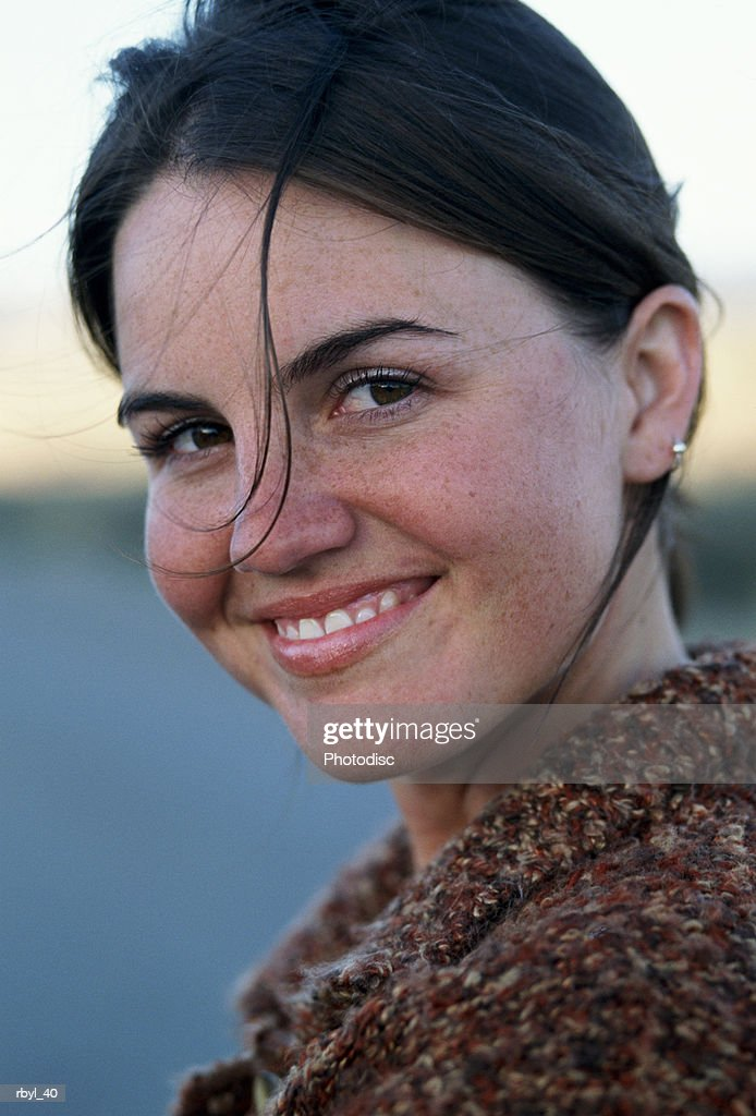a portrait of a young brown haired woman looking at the camera and smiling : Foto de stock